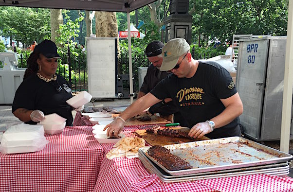 Cutting and plating ribs at Dinosaur BBQ booth
