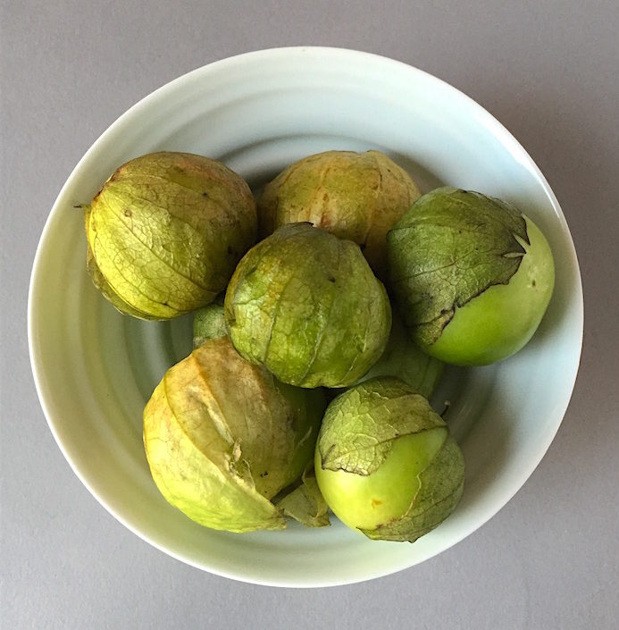 Fresh tomatillos in a porcelain bowl by James Makins